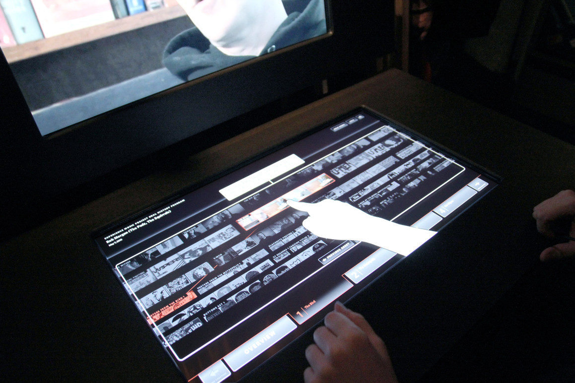 Touchtable help mode. A hand appears showing the user how to interact with the kiosk.