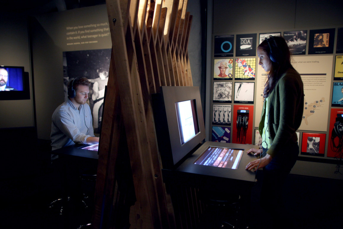 Visitors using the first (of three) interactive touchtable stations to explore an extensive collection of media and oral histories not seen elsewhere in the exhibition.