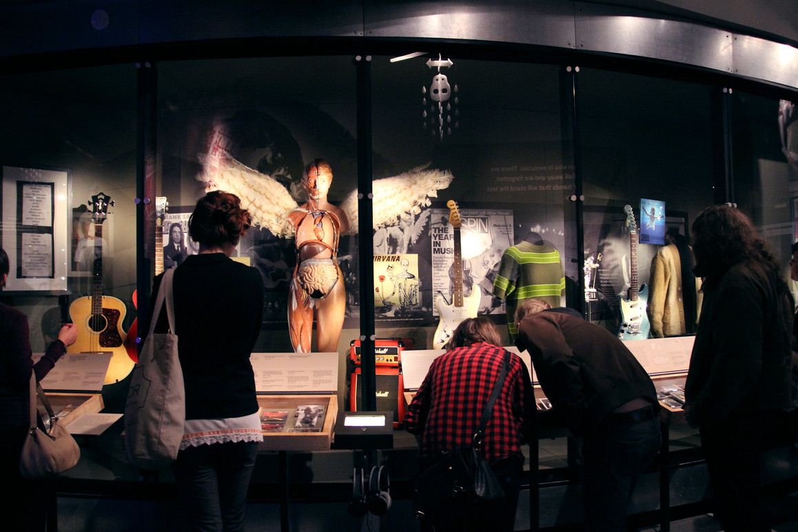 Visitors looking at objects in the long display case with photo murals behind them.